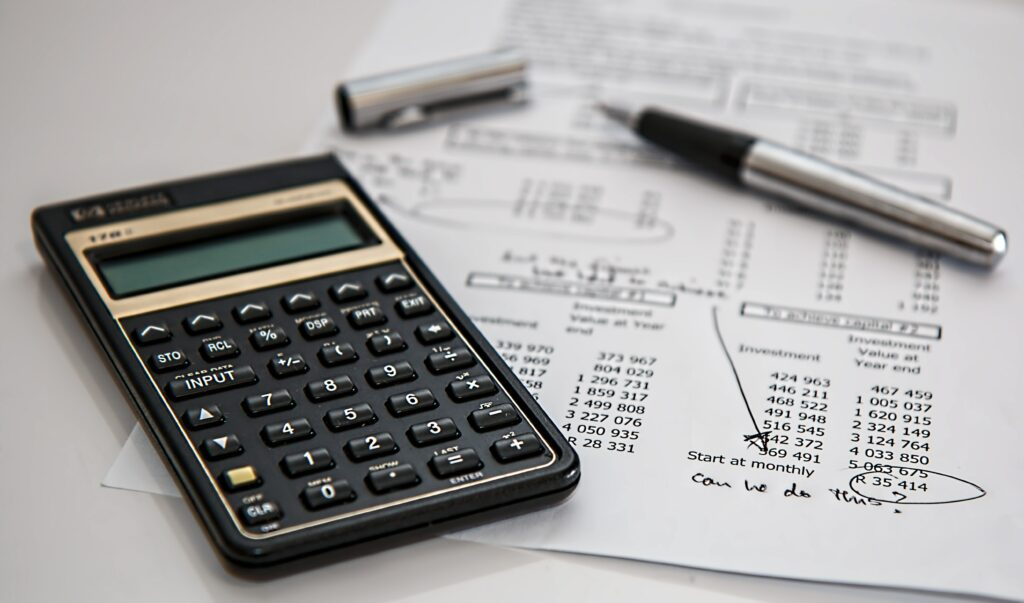 A calculator, pen, and an invoice calculating how to best manage dental practice revenue